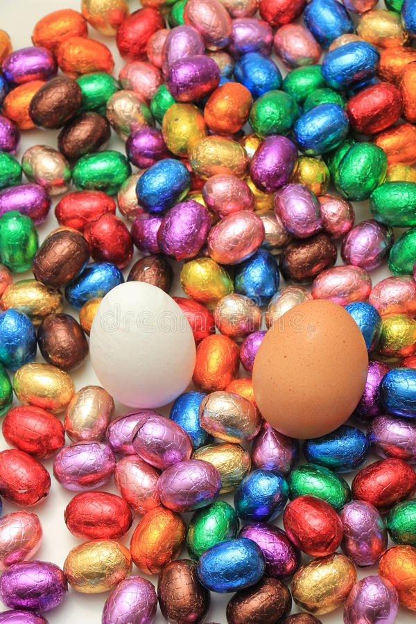 Chocolate and hen easter eggs. Hen eggs on a pile of colorful wrapped chocolate easter eggs stock photo