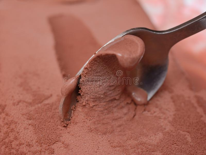 Chocolate ice cream gets a spoon from a briquette, close up. Macro.  stock images
