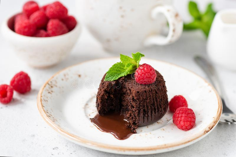 Chocolate lava cake with molten core on white plate. Served with fresh raspberries and mint leaf royalty free stock photography