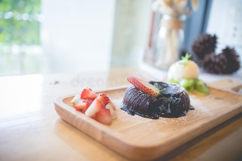 Chocolate lava cake with vanilla ice cream and strawberry. Chocolate lava cake with vamilla ice cream and strawberry. chocolate lava on wood plate. chocolate stock photos