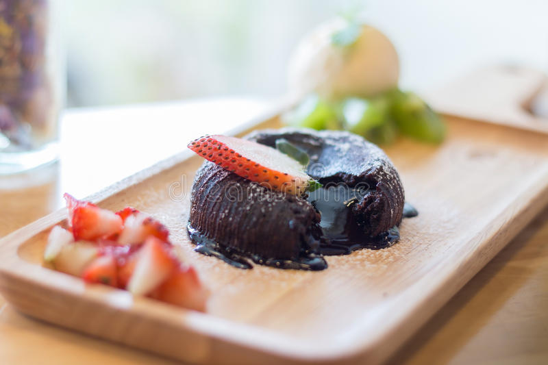 Chocolate lava cake with vanilla ice cream and strawberry. Chocolate lava cake with vamilla ice cream and strawberry. chocolate lava on wood plate. chocolate stock image