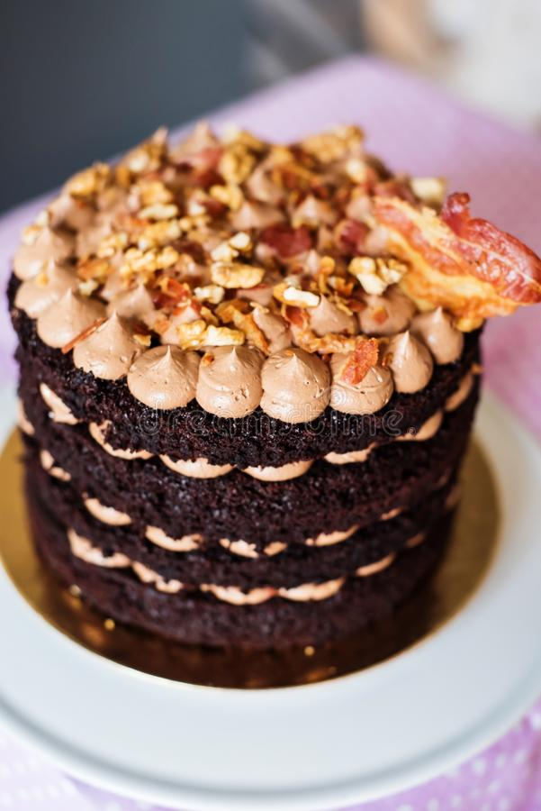 Chocolate layered cake with caramel cream and crispy bacon. Dark chocolate layered cake with caramel butter cream and crispy caramelized bacon, trendy dessert stock photography