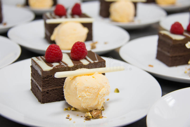 Chocolate layered cake topped with raspberry and ice cream stock photos