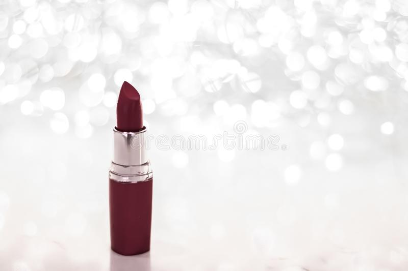 Chocolate lipstick on silver Christmas, New Years and Valentines Day holiday glitter background, make-up and cosmetics product for. Cosmetic branding, sale and stock image