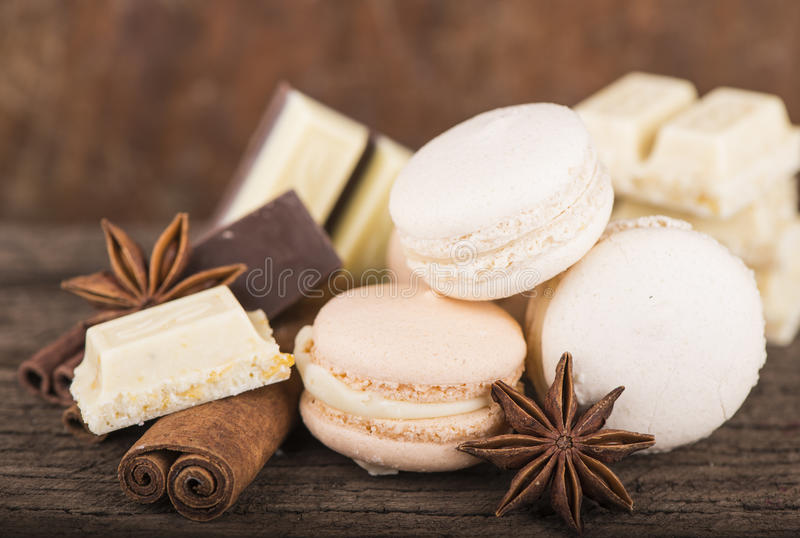 Chocolate macaroons with pieces of white and black chocolate. On old wooden table stock image