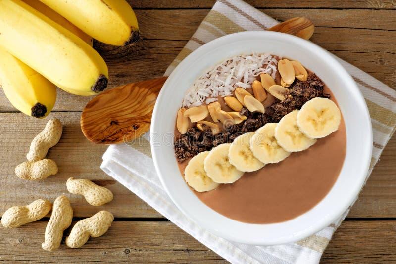 Chocolate, manteiga de amendoim, banana, cena aérea da bacia do batido na madeira rústica fotografia de stock royalty free