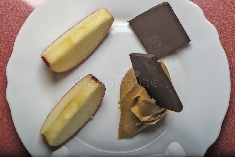 Chocolate, manzanas y mantequilla de cacahuete imagen de archivo