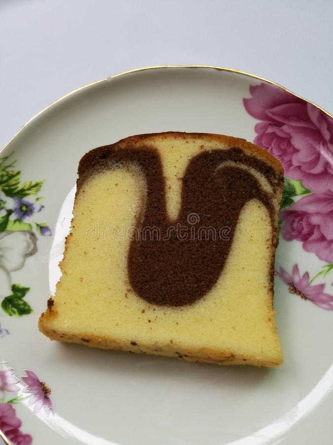 Chocolate marble and butter cake. In ceramic plate isolated on white background stock photography