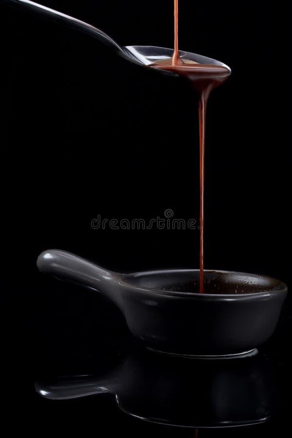 Chocolate marrón lechoso derretido que vierte de una cuchara, aislada en negro foto de archivo libre de regalías