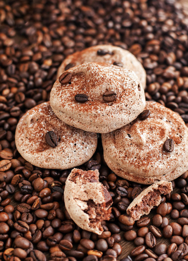 Chocolate meringue cookies. On the coffee beans background royalty free stock images