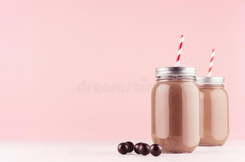 Chocolate milkshake in retro jars with sweet candy balls, red straws in modern stylish pink interior on white wooden table. stock images