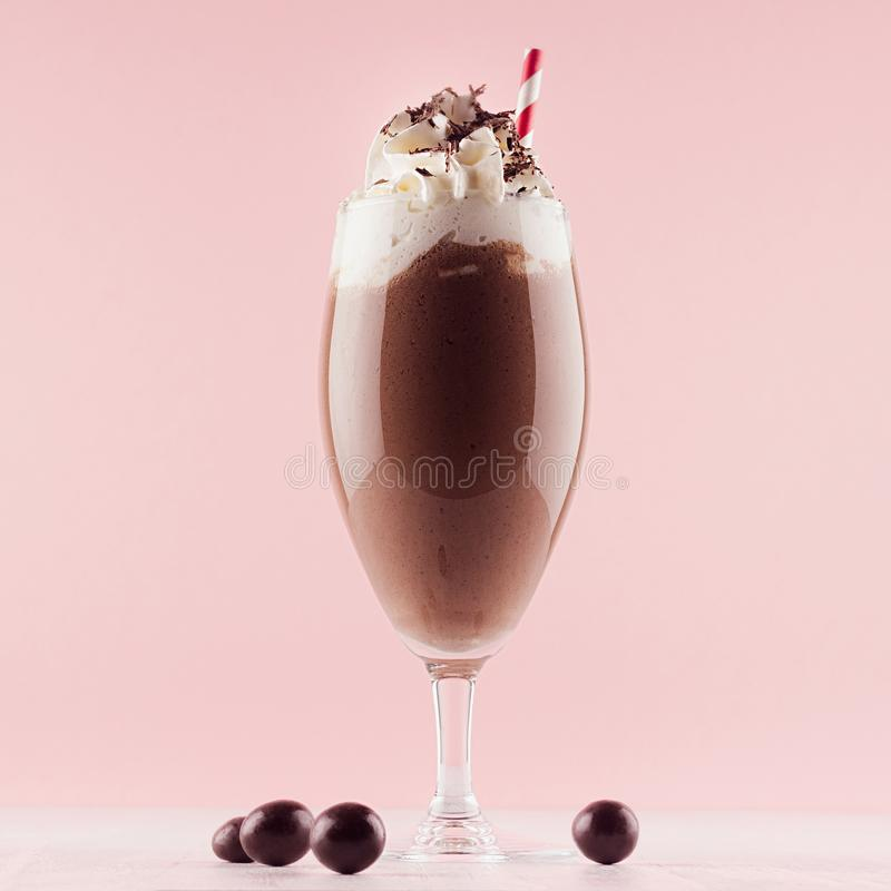 Chocolate milkshake with sweet whipped cream, straw and candies in modern stylish pink interior on white wooden table, square. royalty free stock photo