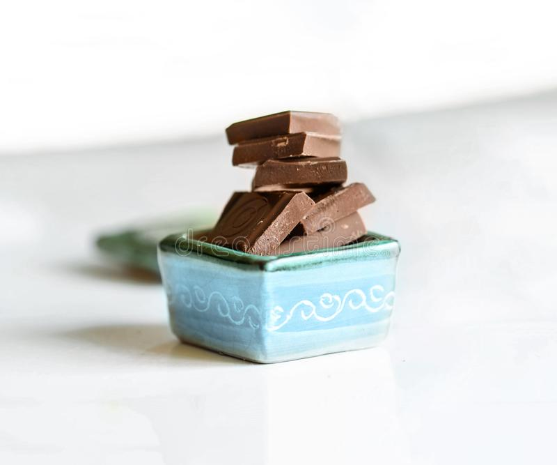 Milk chocolate in a porcelain bowl. Chocolate mood. Milk chocolate in a porcelain bowl stock photo