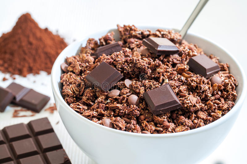 Chocolate Muesli. Extreme close up of white bowl with Chocolate Muesli.Chocolate slab and cacao powder in background royalty free stock photos