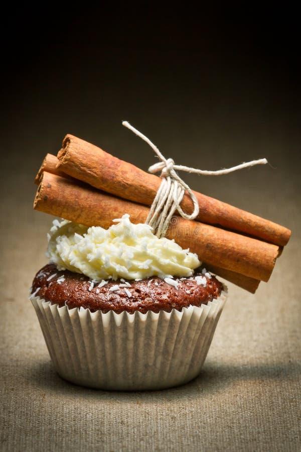 Chocolate muffin with cinnamon bark and cream stock photo