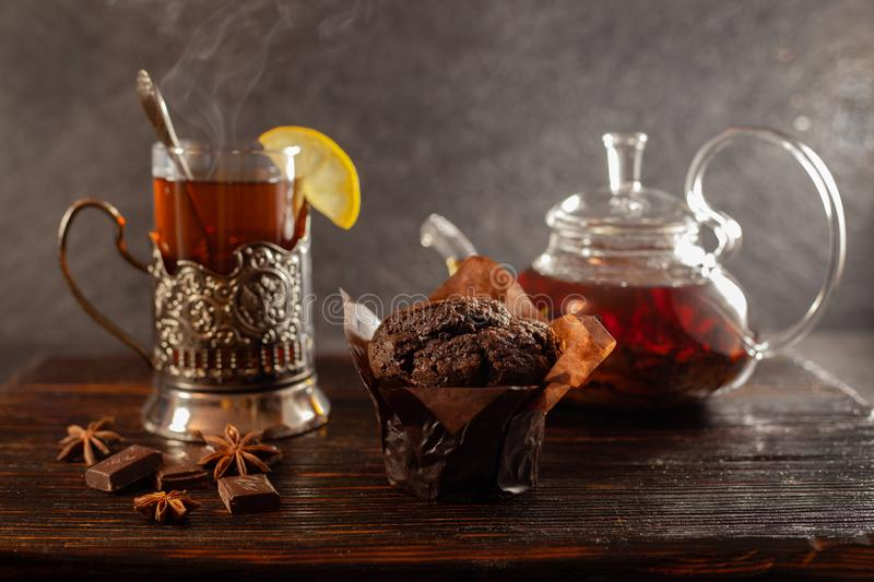 Chocolate muffin, lemon tea, transparent teapot and chocolate on a dark, old wooden board. Blurred background royalty free stock images