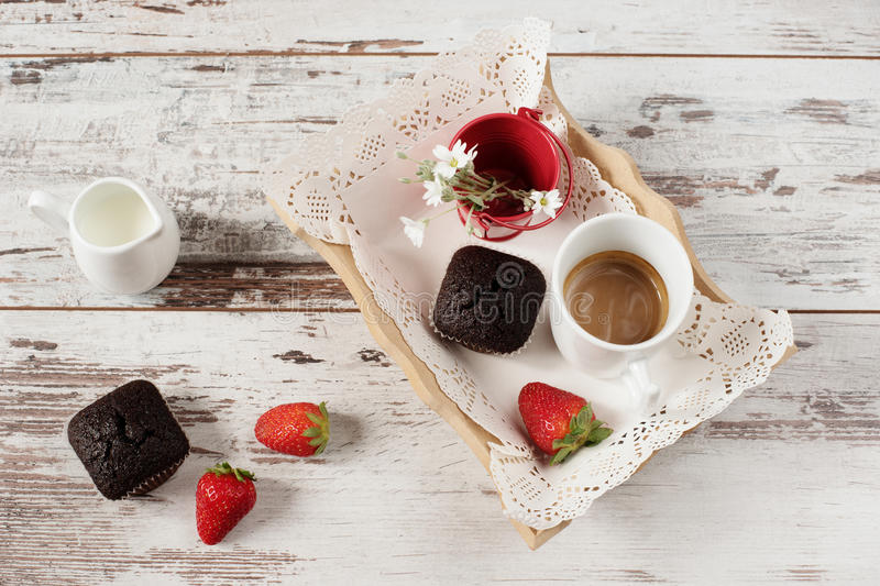 Chocolate muffins, coffee, strawberries, a vase of white flowers. Light wood rustic background stock photography
