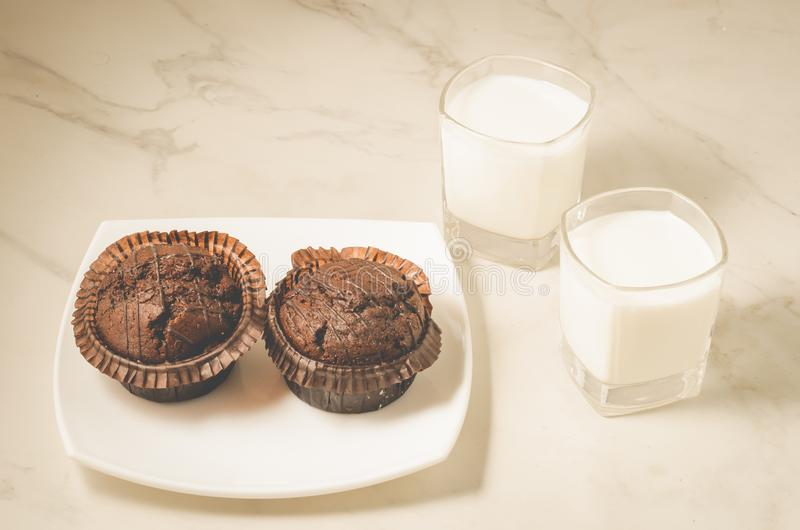 Chocolate muffins and glasses with milk/chocolate muffins and glasses with milk on a white marble background. Selective focus royalty free stock photo