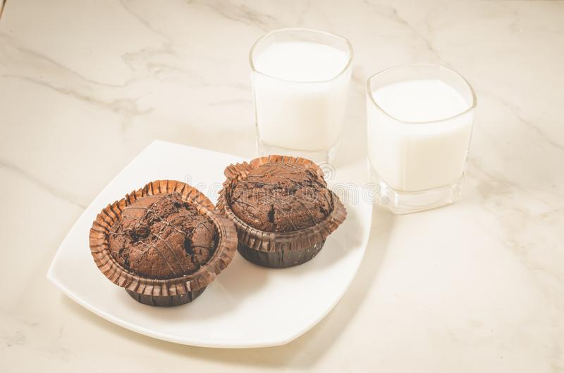 Chocolate muffins and glasses with milk/chocolate muffins in a w stock photos