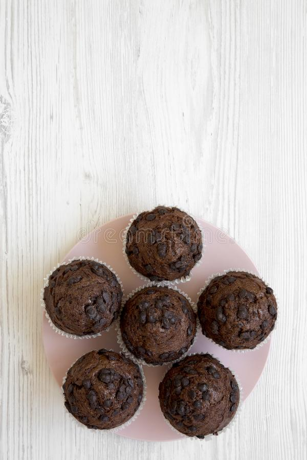 Chocolate muffins on pink plate on white wooden table, top view. Flat lay, overhead, from above. overhead, from above. royalty free stock images