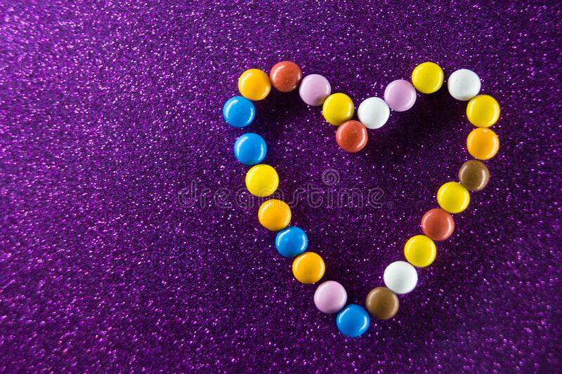 Chocolate multi-colored drops laid out in the shape of a heart on a colored background. A surprise for lovers in the shape of a heart made of colored sweets royalty free stock photo