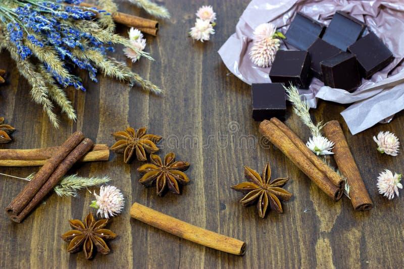 Chocolate natural com flores canela da alfazema e anis de estrela em um fundo de madeira foto de stock