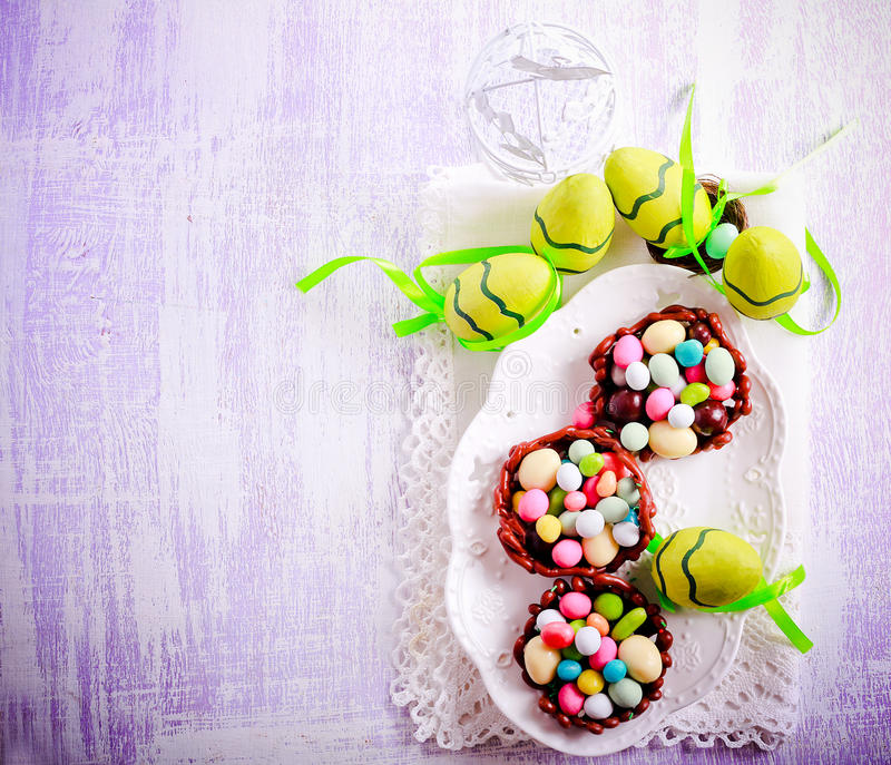 Chocolate nests filled up with egg shaped candies for Easter royalty free stock photo