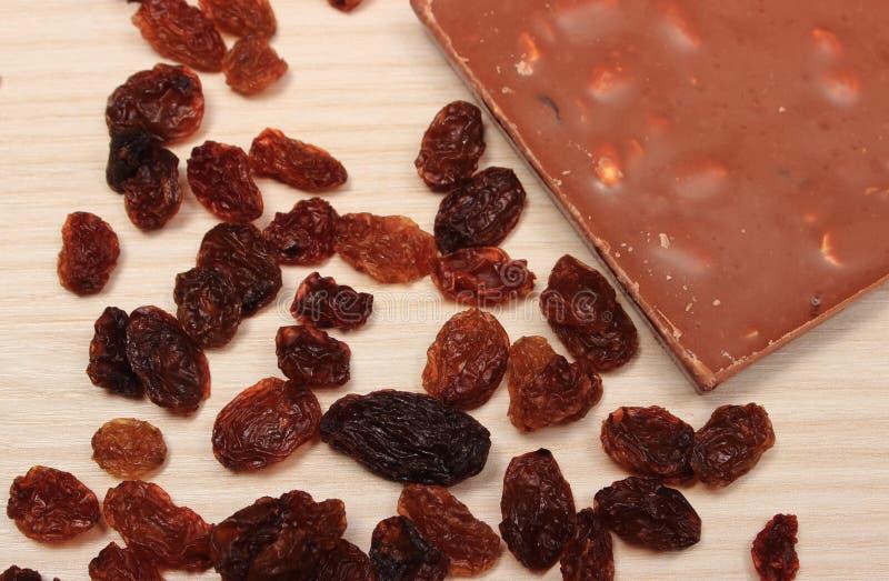 Chocolate nutritivo con las nueces y las pasas en la tabla de madera fotografía de archivo