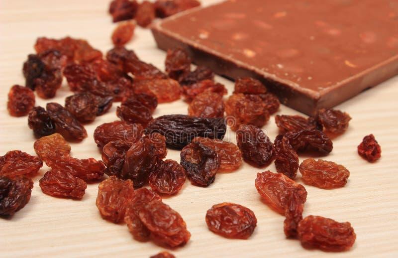 Chocolate nutritivo con las nueces y las pasas en la tabla de madera imagen de archivo