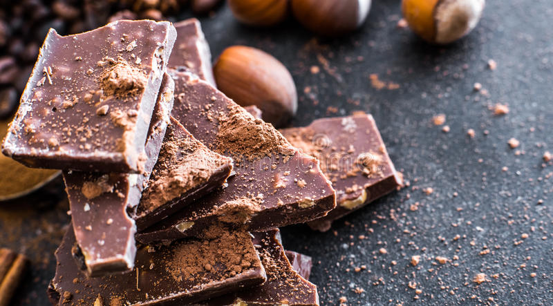 Chocolate and nuts on a black table royalty free stock images