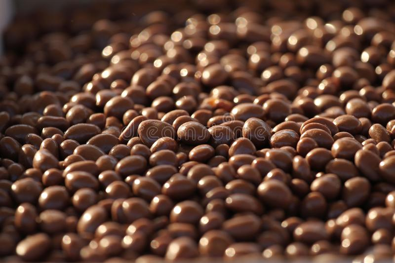 Chocolate nuts. Nuts in chocolate for dessert. Milk chocolate candies. Chocolate background texture. Chocolate nuts. Nuts in chocolate for dessert. Milk stock photo