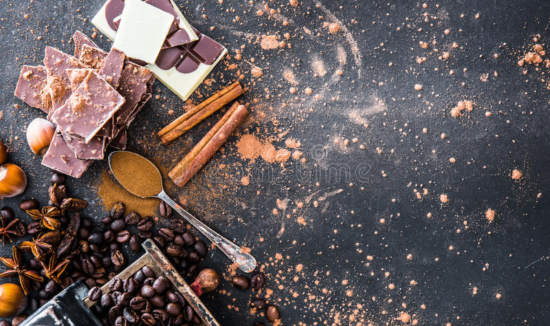 Chocolate, nuts, spices on table stock photography