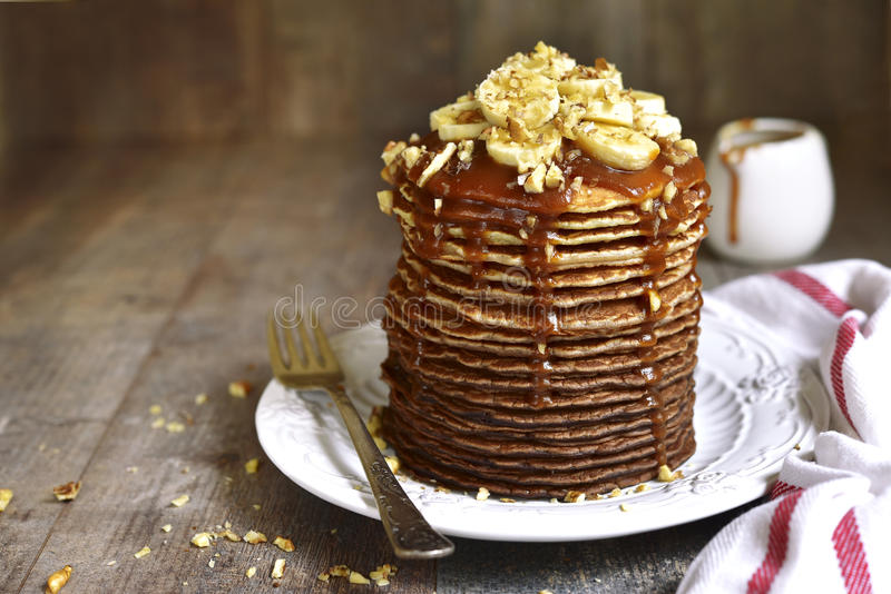 Chocolate ombre pancakes with banana,walnuts and caramel. Chocolate ombre pancakes with banana,walnuts and caramel on a white plate on rustic wooden background stock photography