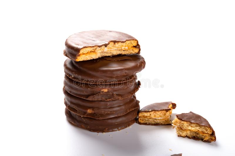Chocolate outer biscuits stacked up with one piece broken on white. Background royalty free stock image