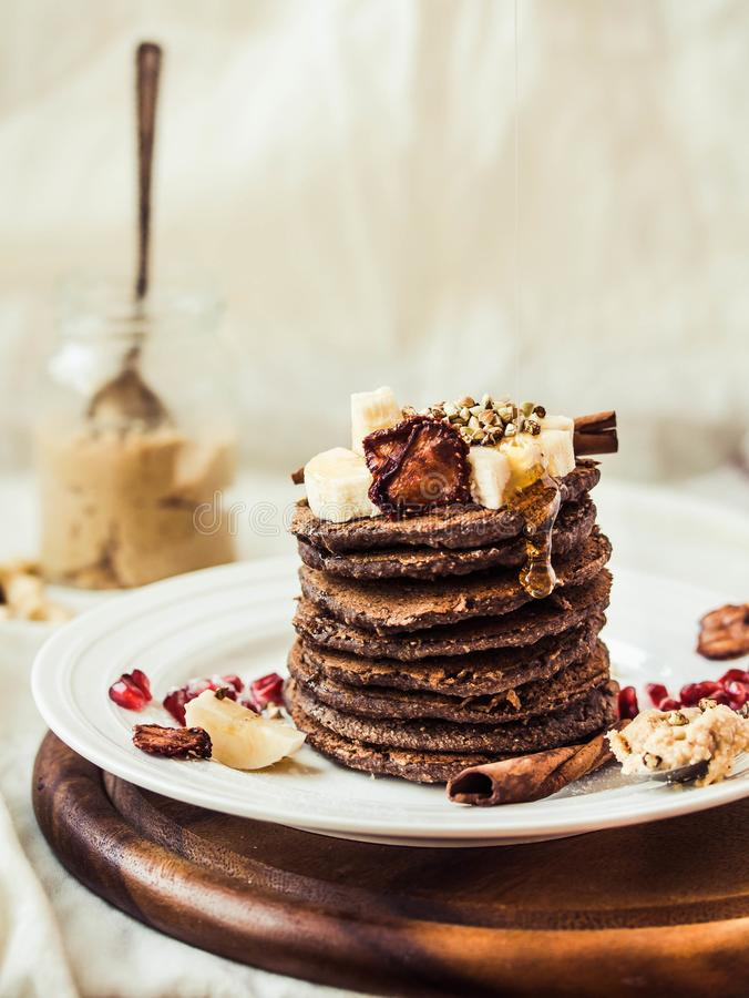 Chocolate pancakes with banana, peanut butter, cinnamon and maple syrup. A healthy breakfast for stock image