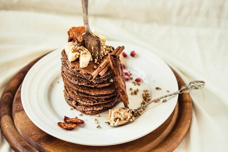 Chocolate pancakes with banana, peanut butter, green buckwheat a royalty free stock photography