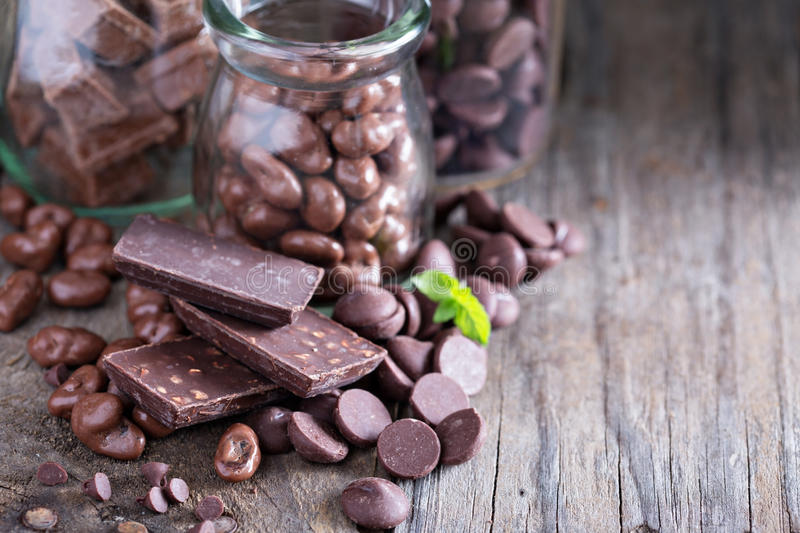 Chocolate pieces, chips, candies and bars. In jars royalty free stock photo