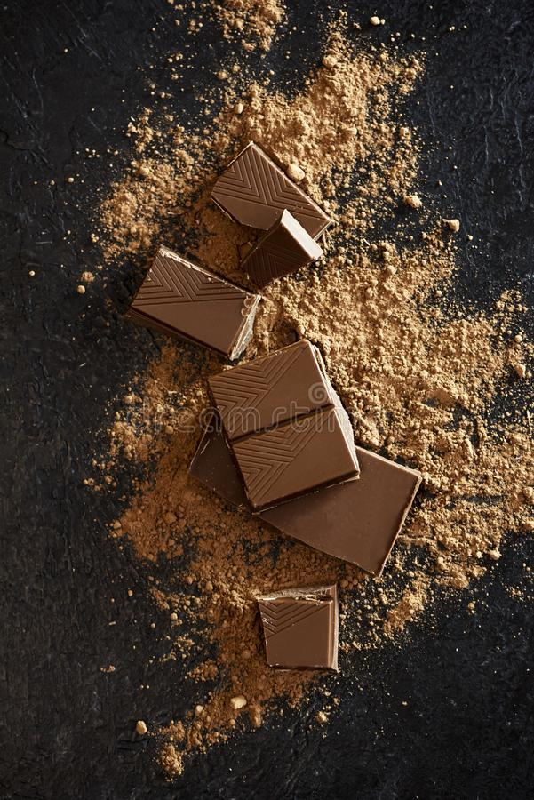 Chocolate pieces and cocoa powder. Broken chocolate pieces and cocoa powder on black. Chunks of chocolate onr dark stone background royalty free stock photography