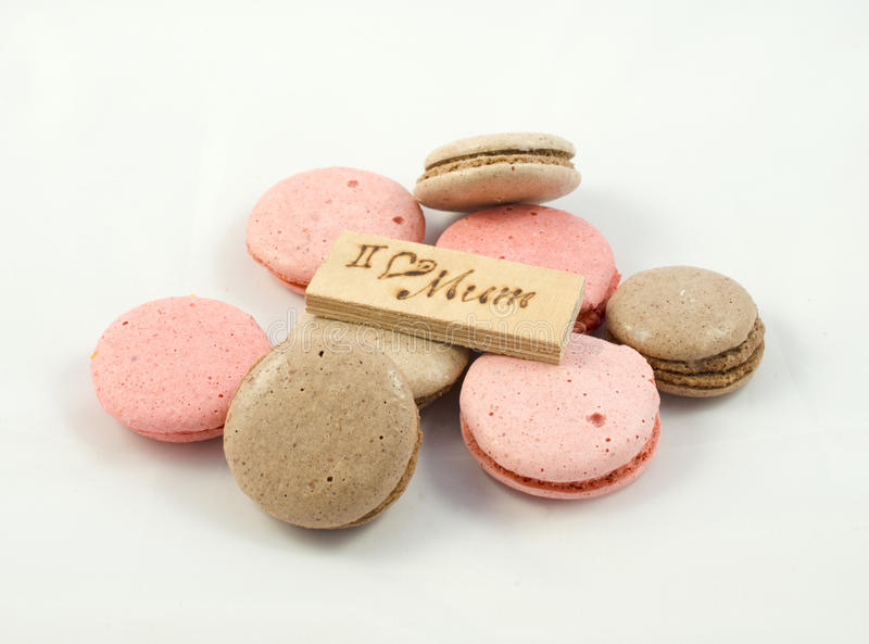 Chocolate and pink macarons chaotically arranged and a board with the inscription I love mum. A Happy Mother's Day theme royalty free stock images