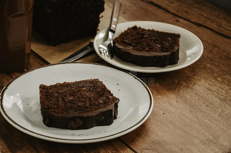 Chocolate pound cake pieces on white plates. Brown toned. royalty free stock photography