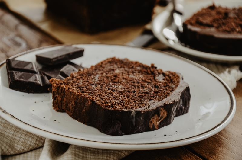 Chocolate pound cake slices on white plates. Brown toned, stock image