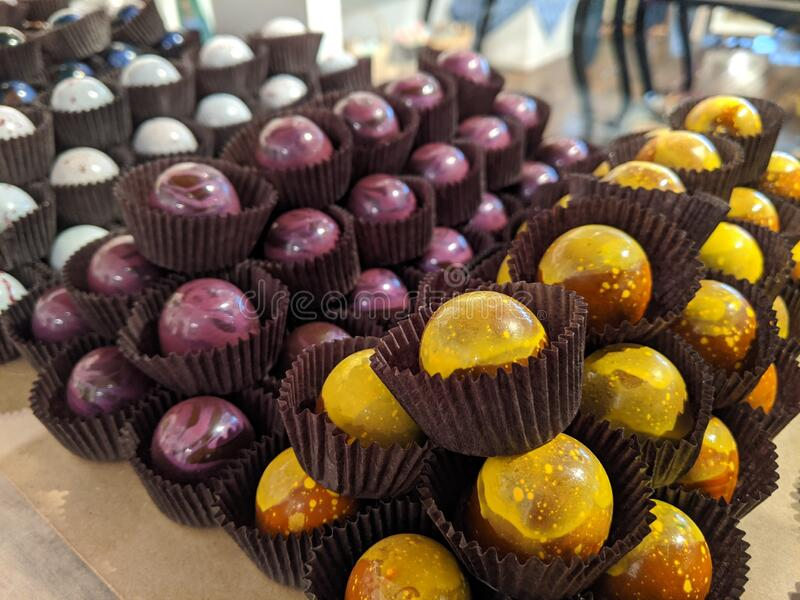 Chocolate powder covered bonbon truffes in yellow purple and white stock photography