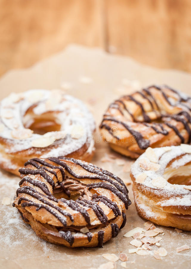 Chocolate and powdered sugar cream puff rings choux pastry royalty free stock photo