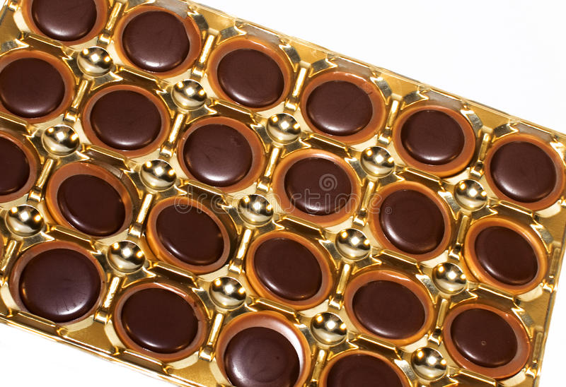 Chocolate pralines. Close-up of chocolate pralines in gold box stock photos