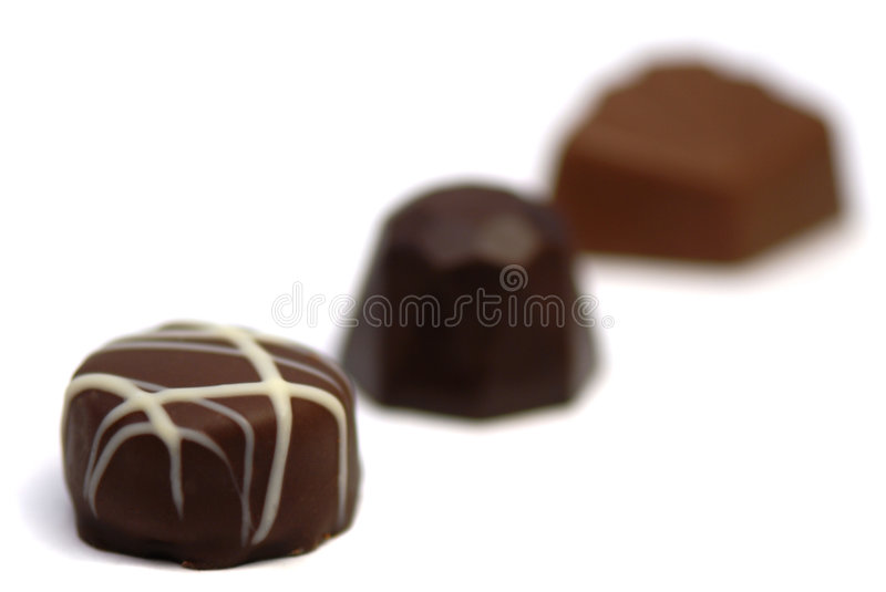 Chocolate pralines. Photo of three chocolate pralines isolated on a white background. shallow focus royalty free stock photos