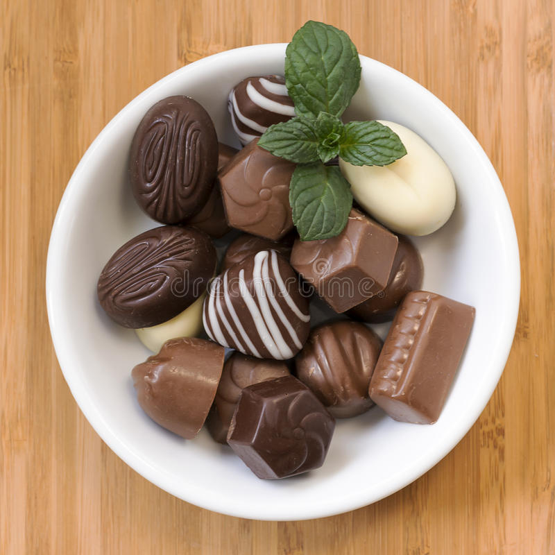 Chocolate pralines. Assorted chocolate pralines with mint on a plate or bowl, top view royalty free stock photography