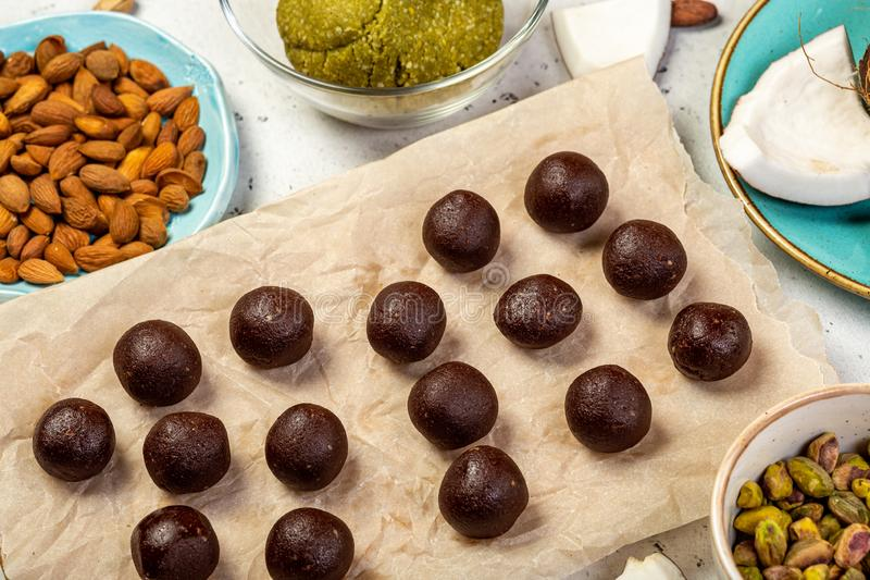 Chocolate pralines balls and other ingredients for making paleo candies. Handmade chocolate pralines balls on baking paper. Step in cooking raw vegan sweets royalty free stock photography