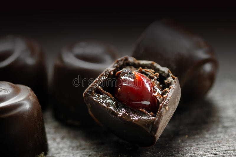 chocolate pralines with red fruit filling on a dark rustic wooden background, makro shot stock photos