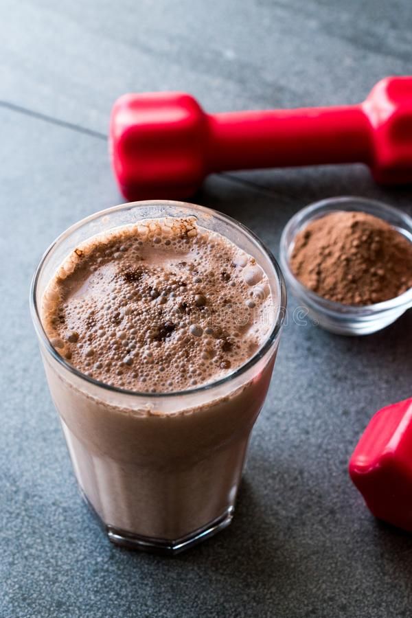Chocolate Protein Shake Smoothie with Whey Protein Powder and Red Dumbbells. Sports Drink stock photo
