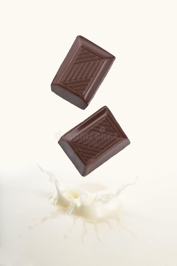 Chocolate que cai no leite imagens de stock royalty free